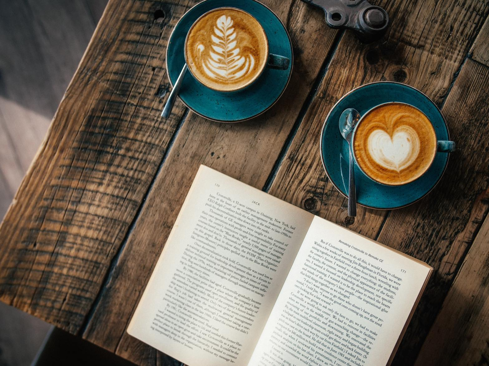Two coffee cups on a wooden table, news to an open book