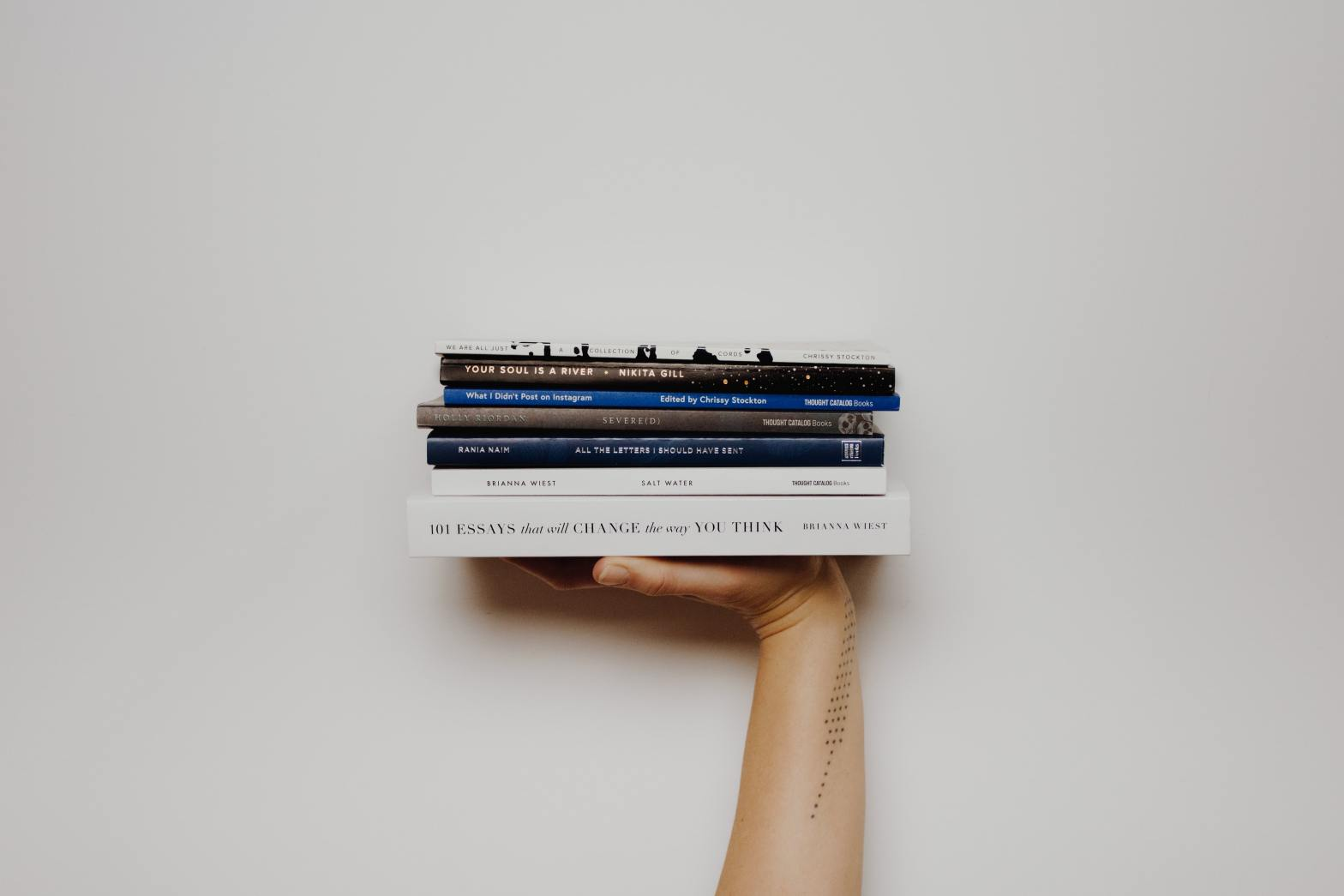 Hand holding stack of books against a white wall