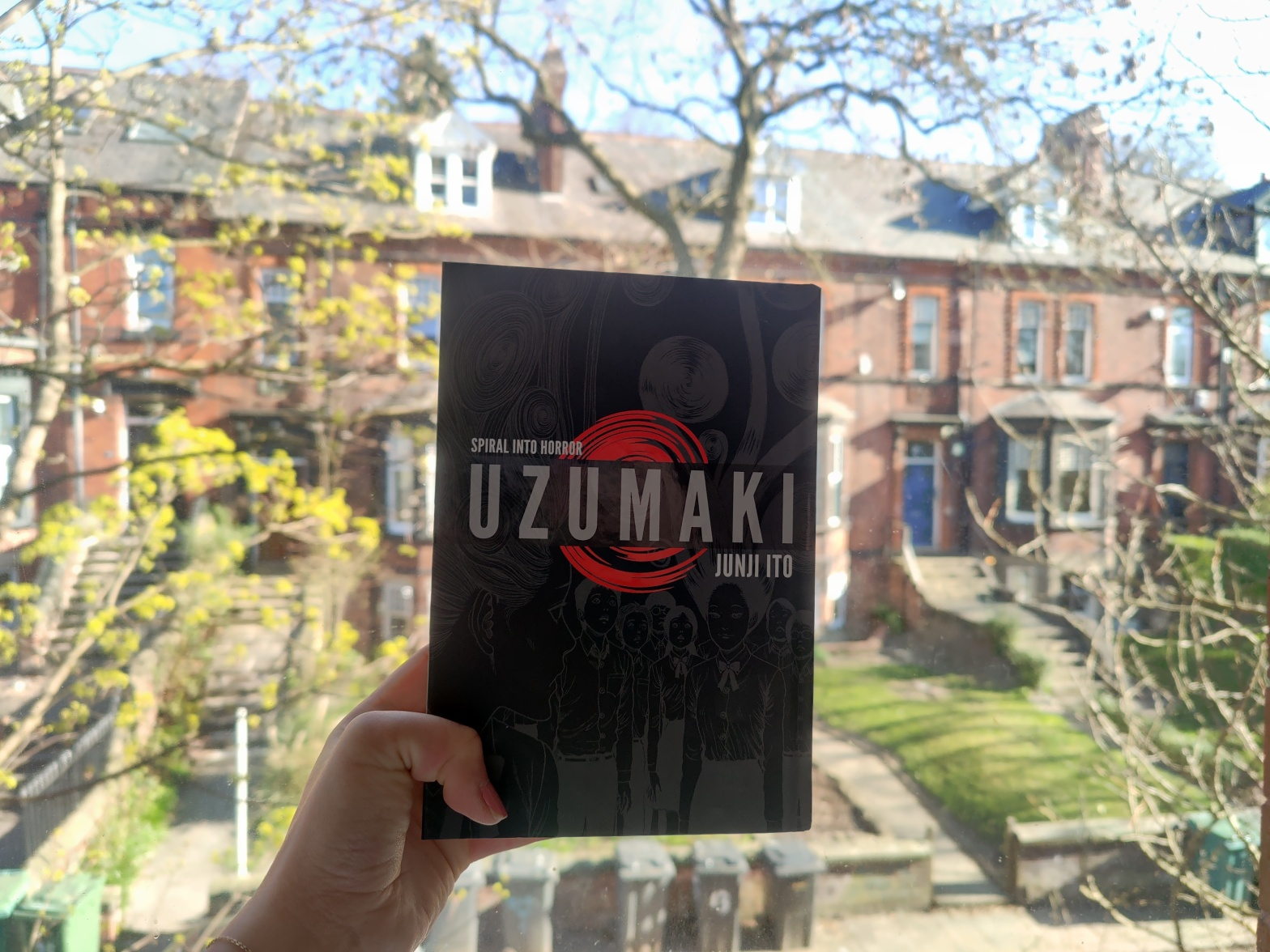 Uzumaki manga held against a bright window on a sunny day, with red-brick buildings in the background