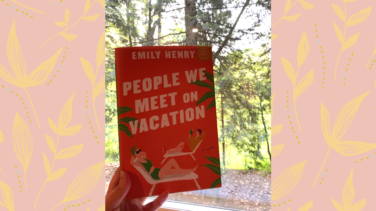 A hand holding the book 'People we meet on vacation' against a window in a forest, on a pale pink background with a yellow leaves pattern.