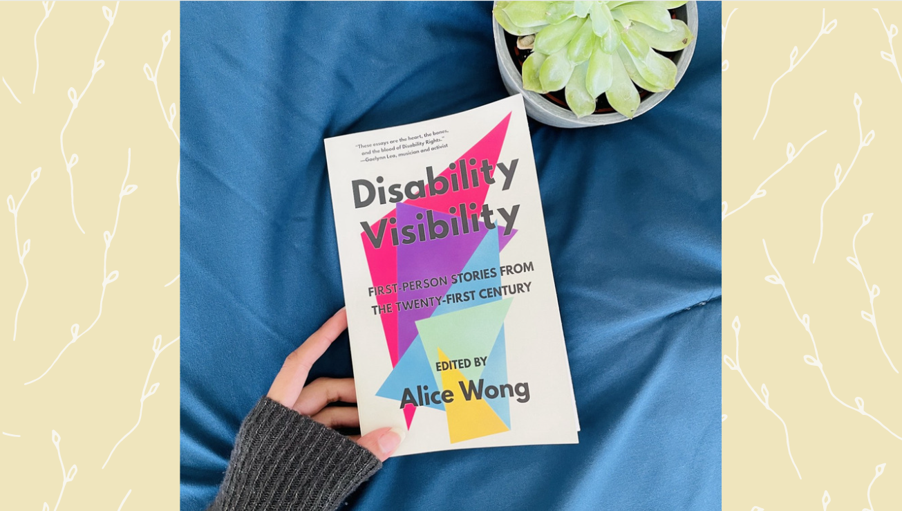 The book 'Disability Visibility' on a blue fabric, with a plant pot in the upper right corner.