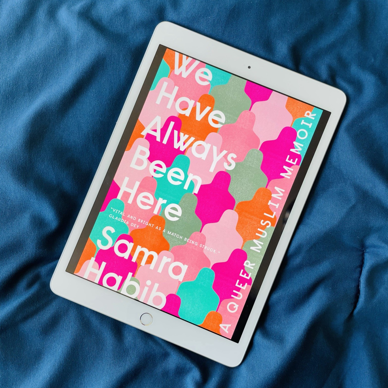 White e-reader on a satin navy fabric showing the cover of 'We have always been here', a queer Muslim memoir.