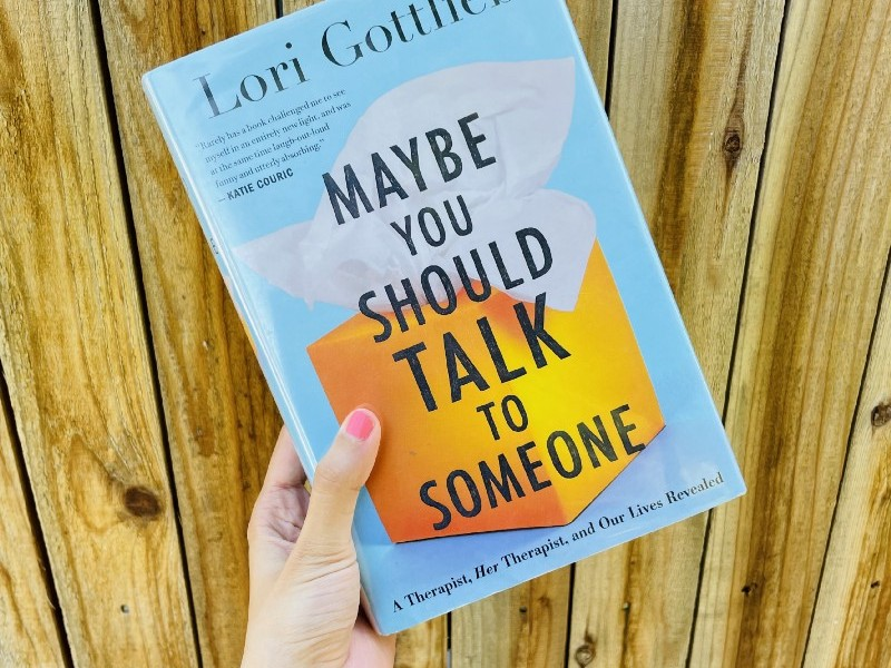Hand holding 'Maybe you should talk to someone' against a wooden background. The cover is light blue with an orange box of tissues in the middle.