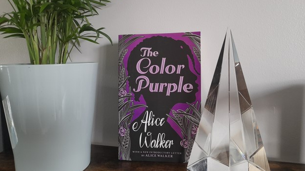 Copy of 'The Color Purple' on a wooden shelf, with a plant and a crystal décor object on either side.