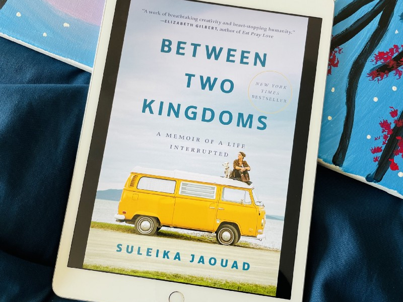 Suleika Jaouad's memoir, Between Two Kingdoms, atop a navy blue comforter. A painting with blue, black, yellow, and purple sits in the bottom half of the photo, behind the book.