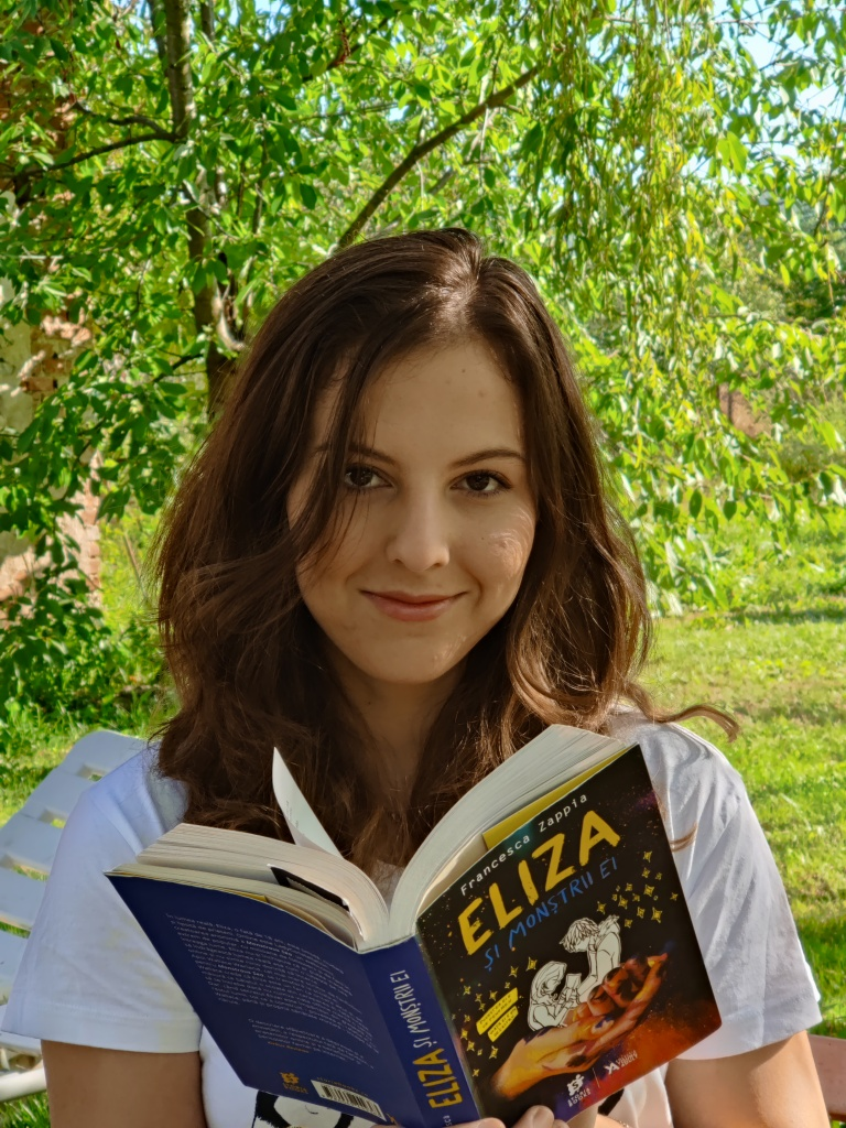 """Eliza Lita reading Francesca Zappia's """"Eliza and her monsters"""" under a willow tree on a sunny day, smiling."""