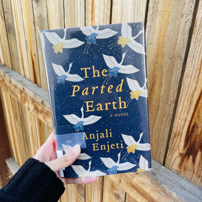 Copy of A Parted Earth, held up against a wooden fence